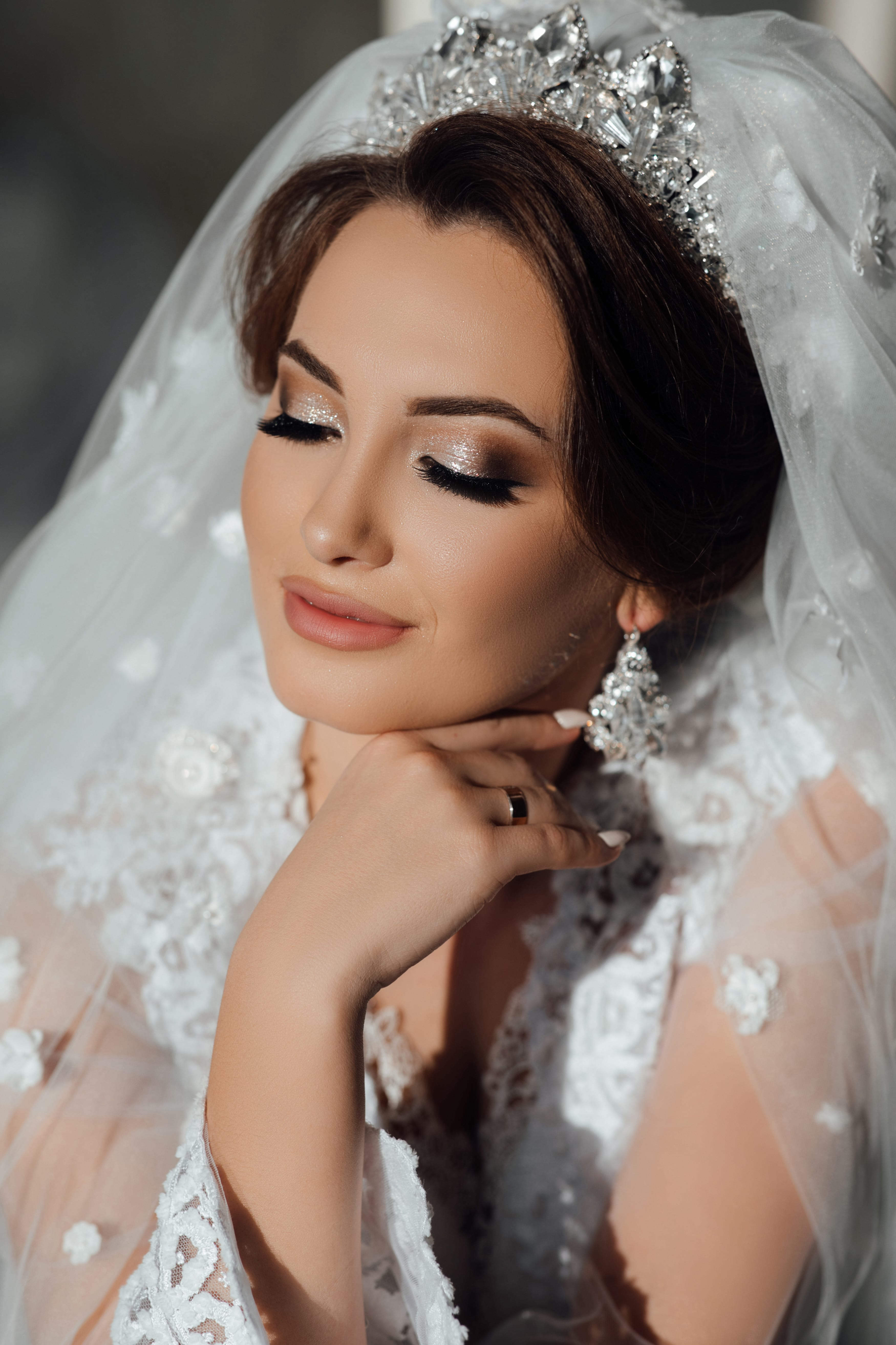Bride wedding morning. Fashion bride gorgeous beauty, bride woman in robe. Bride touches earrings. Portrait wedding makeup and hairstyle, girl with veil and jewelry at home.
