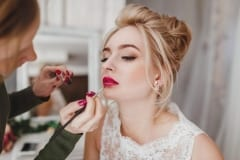 Professional stylist doing make-up for blonde woman
